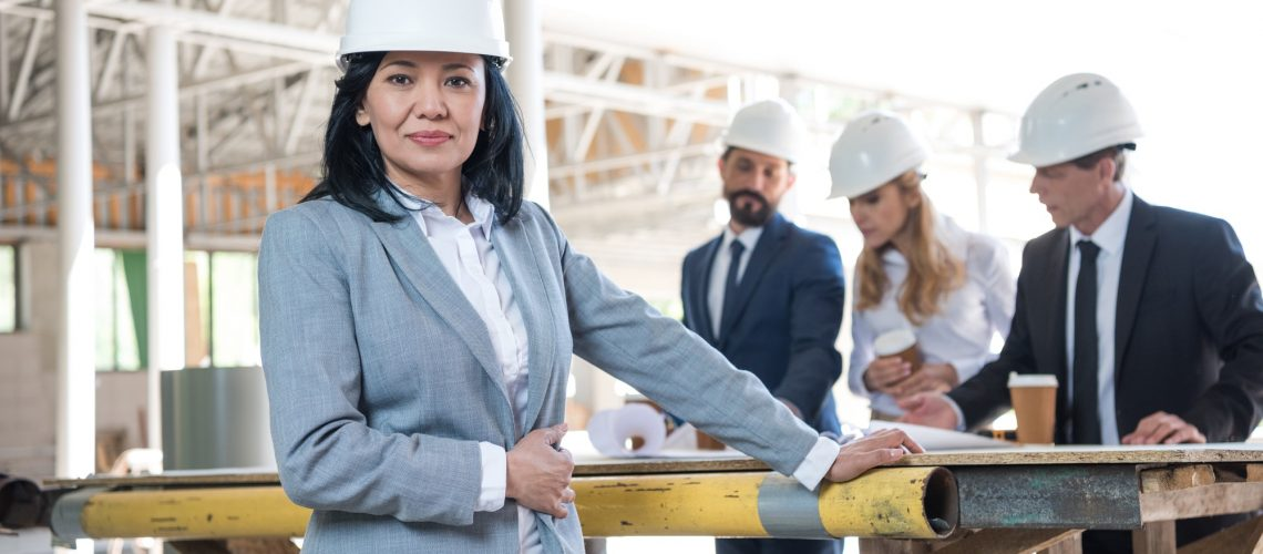 middle aged asian contractor looking at camera during meeting at construction site
