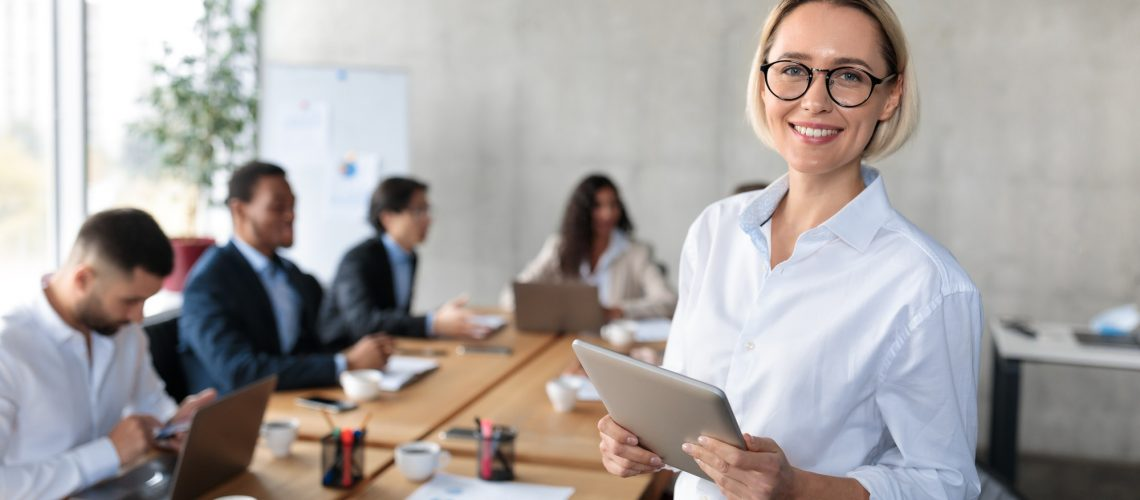 Successful Businesswoman Holding Digital Tablet Standing In Modern Office
